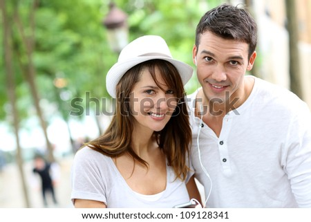 Couple in town using smartphone and handsfree device - stock photo