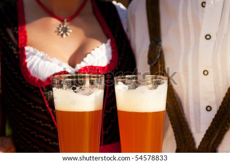 Couple in traditional Bavarian Tracht - Dirndl and Lederhosen - in a beer tent at the Oktoberfest or in a beer garden enjoying a glass of tasty wheat beer, only glasses and torsos to be seen - stock photo