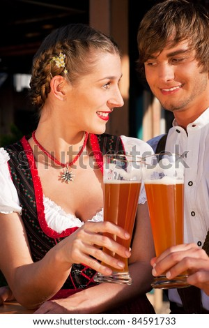 Couple in traditional Bavarian Tracht - Dirndl and Lederhosen - in front of a beer tent at the Oktoberfest or in a beer garden enjoying a glass of tasty wheat beer - stock photo