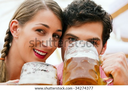 Couple in traditional German costume in a beer tent having a drink - stock photo