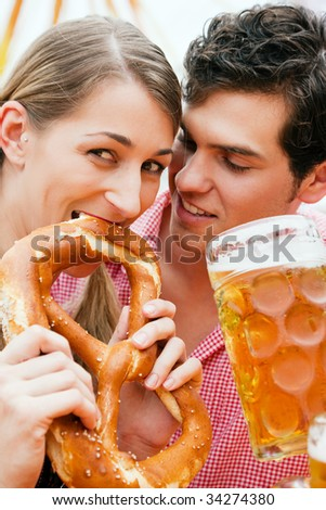 Couple in traditional German costume in a beer tent, he is having a drink, she a pretzel - stock photo