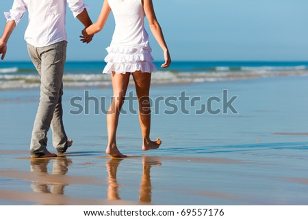 Couple in vacation having a walk on beach in summer, only torso to be seen, they are holding hands - stock photo
