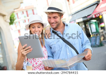 Couple in vacation looking at tourist guide on internet - stock photo