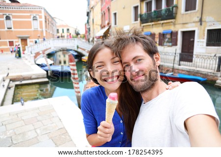 Couple in Venice, eating Ice cream taking selfie self-portrait photo on vacation travel in Italy. Smiling happy Asian woman and Caucasian man in love having fun eating italian gelato food outdoors. - stock photo