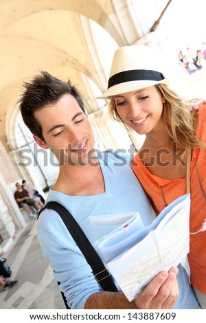 Couple in Venice reading map under the arcades of Palazzio Ducale