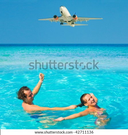 couple in water and some more in the plane overhead - stock photo