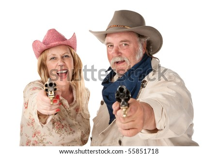 Couple in western wear pointing pistols and laughing - stock photo