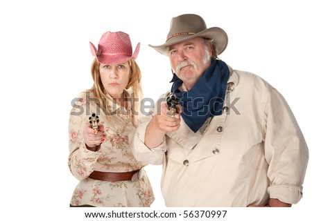 Couple in western wear pointing pistols with serious faces - stock photo