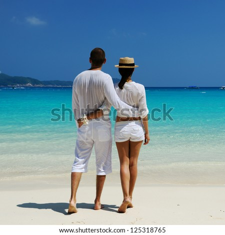 Couple in white on a tropical beach - stock photo