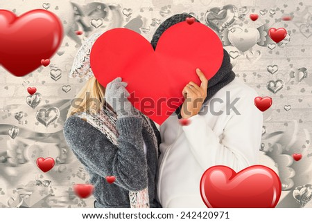Couple in winter fashion posing with heart shape against grey valentines heart pattern - stock photo