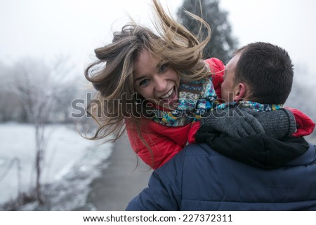 Couple in winter forest near lake - stock photo