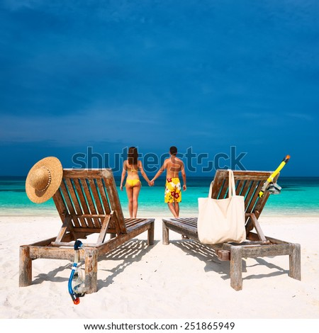 Couple in yellow on a tropical beach at Maldives - stock photo