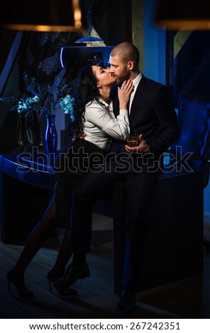 Couple indoors. Sensual brunette and handsome businessman kissing. Office romance concept - stock photo