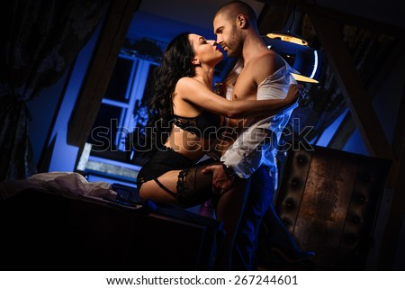 Couple indoors. Sensual brunette in black lingerie and handsome man kissing. Office romance concept - stock photo