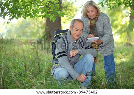 Couple inspecting plants in the forest and making a log - stock photo