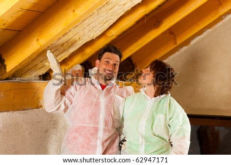 Couple installing thermal insulation thru glass wool on their roof, they are looking pretty proud - stock photo