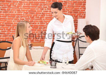couple interacting with waitress at a dinner - stock photo