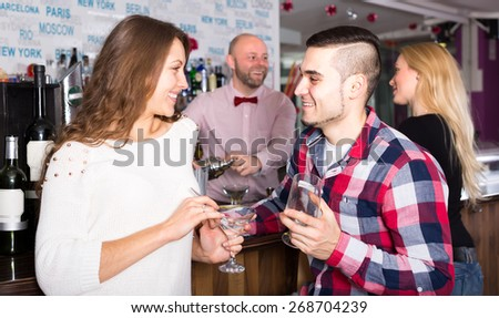 Couple is chatting at the bar while a cheerful bartender is pouring cocktails for another female visitor