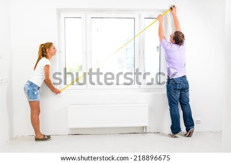 couple is measuring their new empty apartment - stock photo