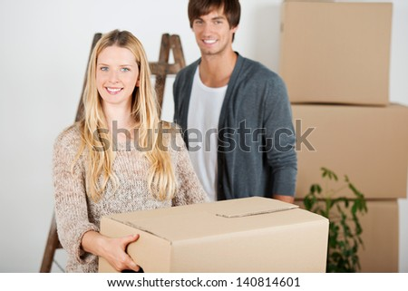 couple is moving and carrying transport boxes - stock photo