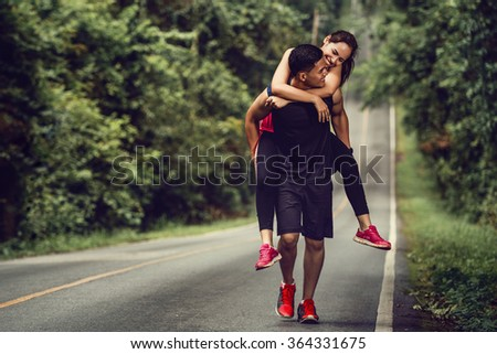 Couple jogging Based on a high Woman to her boyfriend Take her to the finish line. - stock photo
