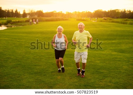 Couple jogging on grass. Senior man and woman smiling. Active leisure of pensioners. Save your health.