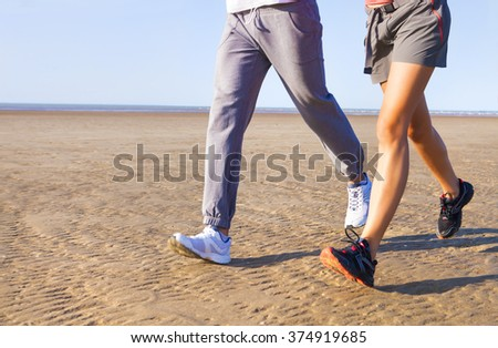 Couple jogging outside, runners training outdoors working out in nature against blue sky with sunset light. Close up - stock photo