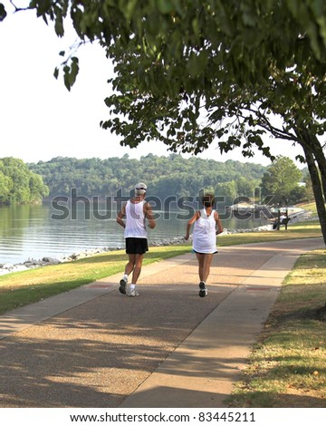 Couple jogging through park along the river - stock photo