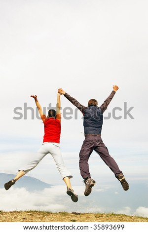 Couple jumping against blue sky - stock photo
