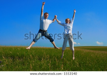 couple jumping in field under blue sky - stock photo