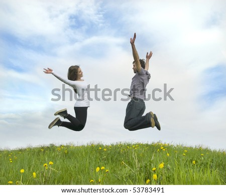 Couple jumping on a meadow - stock photo