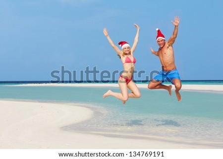 Couple Jumping On Beach Wearing Santa Hats - stock photo