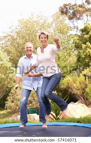 Couple Jumping On Trampoline In Garden - stock photo