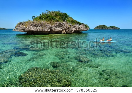 Couple kayaking by a beautiful island beach with pristine waters in the Hundred Islands, Philippines. - stock photo