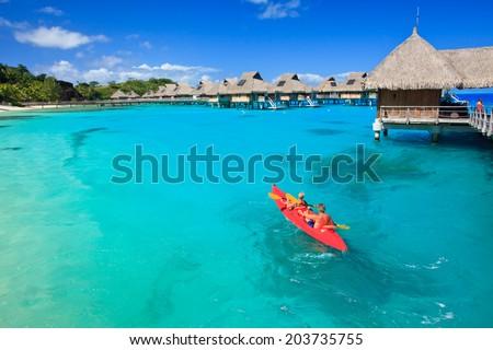 Couple kayaking in the blue lagoon, Bora Bora, French Polynesia, South Pacific - stock photo