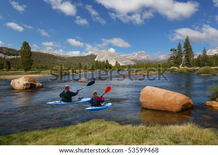 Couple kayaking in the river - stock photo
