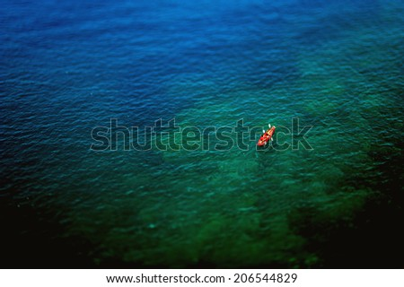 Couple kayaking in wide blue sea as seen from above. Tilt-shift lens used to emphasize the rowers - stock photo