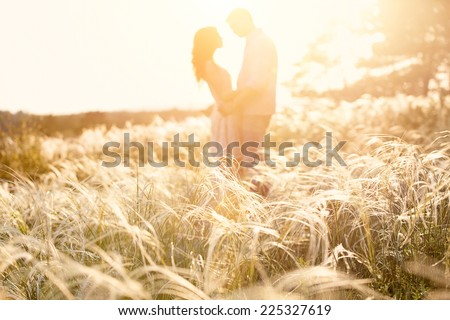 couple kiss at sunset, focus on foreground - stock photo