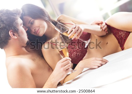 Couple kissing and drinking champagne on the bed in bedroom - stock photo