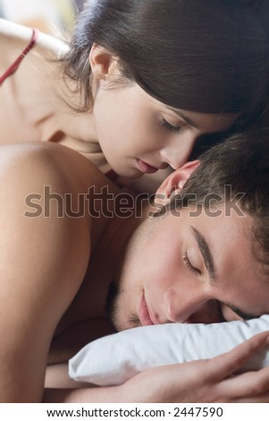 Couple kissing and hugging on the bed in bedroom