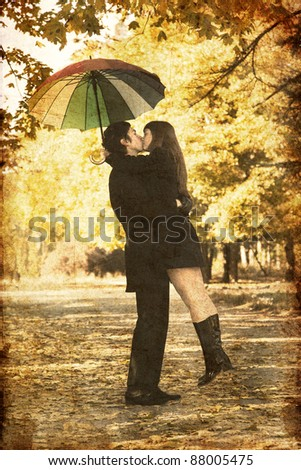 Couple kissing at alley in the park. Photo in old image color style. - stock photo