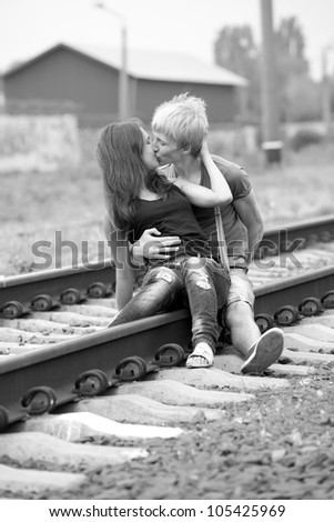 Couple kissing at railway. Photo in black and white style. - stock photo