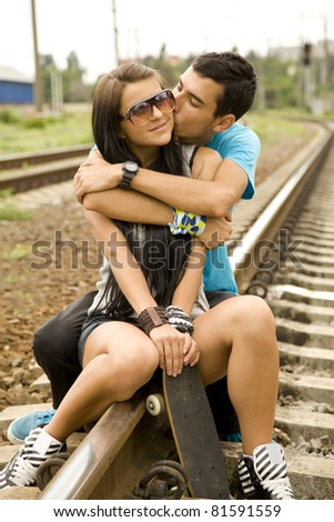 Couple kissing at railway. Urban photo. - stock photo