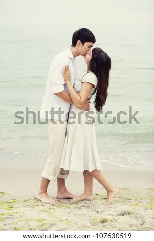 Couple kissing at the beach - stock photo