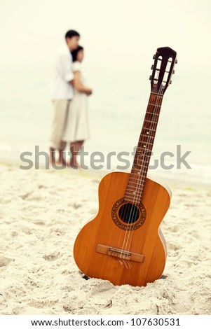 Couple kissing at the beach and guitar. - stock photo