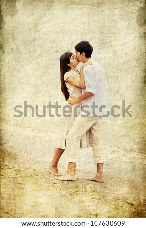 Couple kissing at the beach. Photo in old colour image style. - stock photo