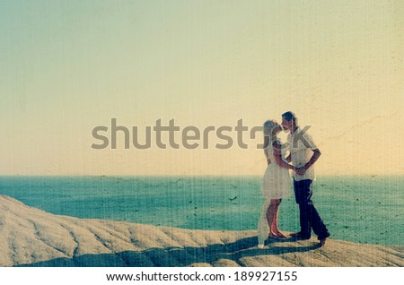 Couple kissing by the sea while standing on a rock. Filtered image: vintage, grunge and texture effects - stock photo