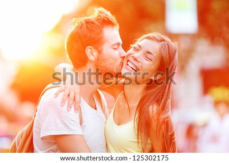Couple kissing happiness fun. Interracial young couple embracing laughing on date. Caucasian man, Asian woman on Manhattan, New York City, USA. - stock photo