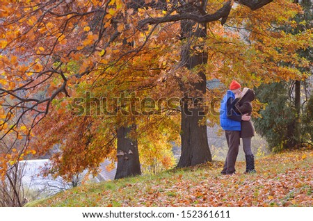 Couple kissing in autumn park on a sunny day - stock photo