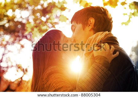Couple kissing in the park at sunset. Photo in multicolor image style. - stock photo